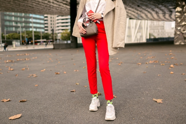 Крупным планом детали моды, молодая женщина в модных красных штанах, забавные носки и уродливые модные кроссовки, бежевое элегантное пальто, позирует на улице возле бизнес-центров, осеннее время.