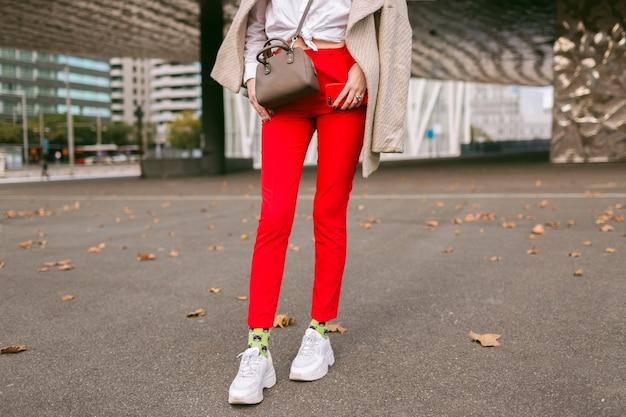ファッションの詳細、トレンディな赤いパンツ面白いソックスと醜いファッションスニーカーを身に着けている若い女性、ベージュのエレガントなコート、ビジネスセンター近くの路上でポーズ、秋の時間を閉じます。