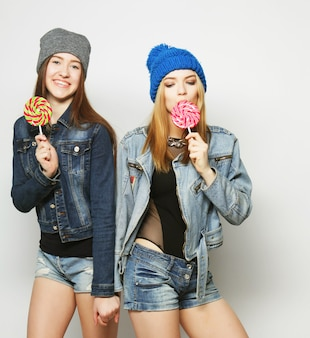 Close up fashion lifestyle portrait of two young hipster girls best friends, holding candys, making funny faces and have good time.
