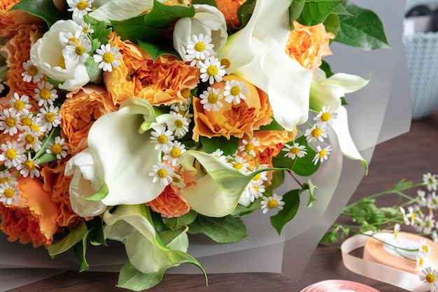 Close up of fashion modern bouquet of different flowers on wooden surface. masterclass. gift for bride on wedding, mother's, woman's day. romantic spring fashion. bright colors of feelings.