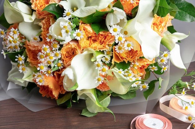 Close up of fashion modern bouquet of different flowers on wooden surface