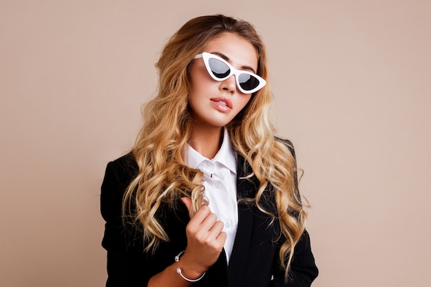 Close up fashion portrait of gorgeous blond woman in stylish casual black jacket posing on beige wall. white retro glasses. hight fashion look.