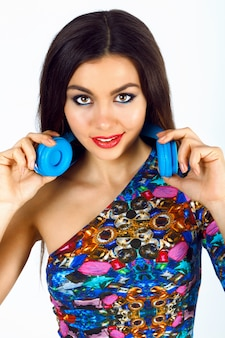 Close up fashion portrait of gorgeous young woman with bright sexy makeup, wearing bright top and big blue dj earphones.