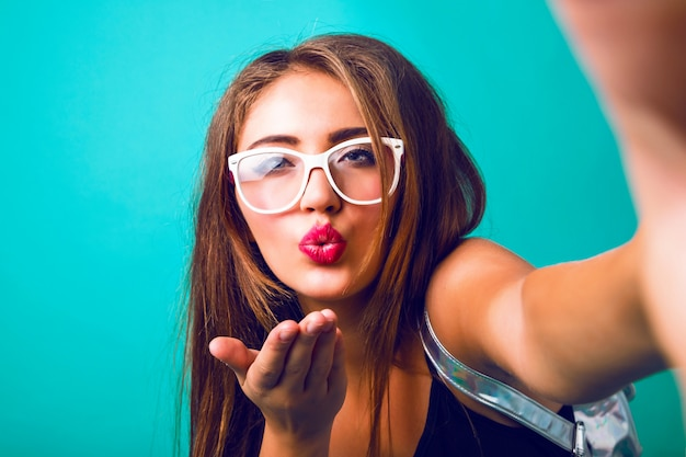 Close up fashion portrait of hipster woman with vintage sunglasses blowing air kiss
