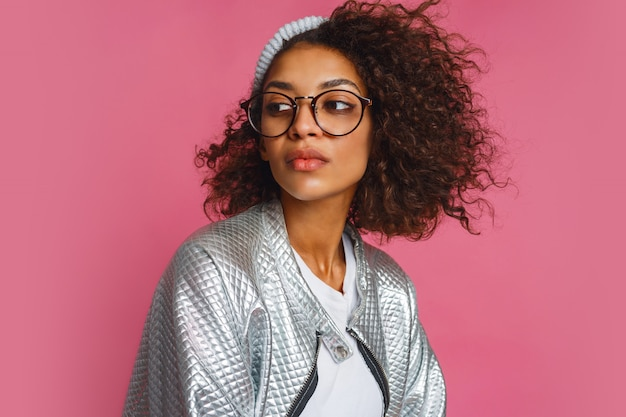 Close up fashion portrait of  mix race woman with brown skin and curly african hairstyle on vivid pink background. wearing silver winter  jacket and grey hat.