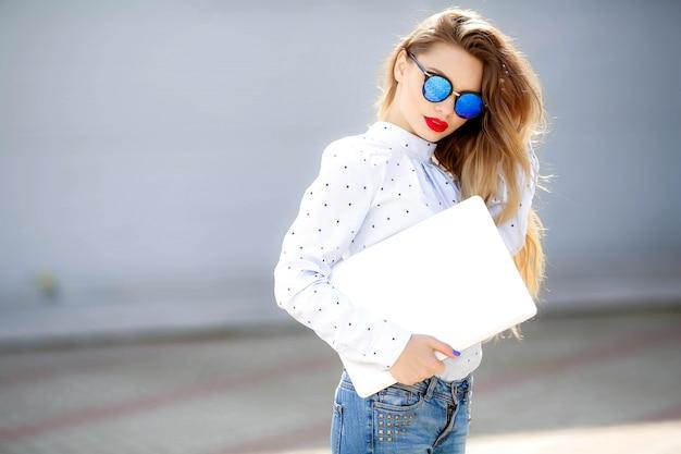 長い髪のジーンズの魅力的な女性のファッションの肖像画を閉じます。ジーンズのスーツの女の子。新しいデニムの衣装を持つ魅力的な女性。街で幸せな若い女