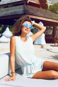 トレンディな丸いミラーサングラス、明るい背景を身に着けている完璧なブロンズ肌の美しいブルネットの少女のファッションポートレートを閉じます。