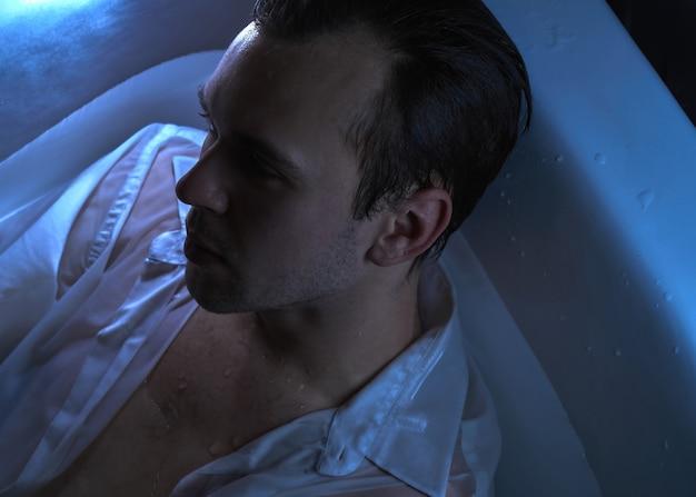 Крупным планом модный портрет кавказского красивого небритого мужчины в ванной в сексуальной мокрой белой рубашке, смотрящего в сторону сильным лицом