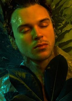 Макро портрет моды кавказского красивого небритого человека под водой в сексуальной мокрой белой рубашке с закрытыми глазами сильное лицо, фон растений