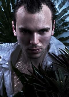 Крупным планом портрет моды кавказского красивого небритого человека под водой в сексуальной мокрой белой рубашке, смотрящего на сильное лицо камеры, фон растений