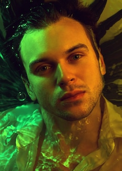 Макро портрет моды кавказского красивого небритого человека под водой в сексуальной мокрой белой рубашке, смотрящего на сильное лицо камеры, фон растений