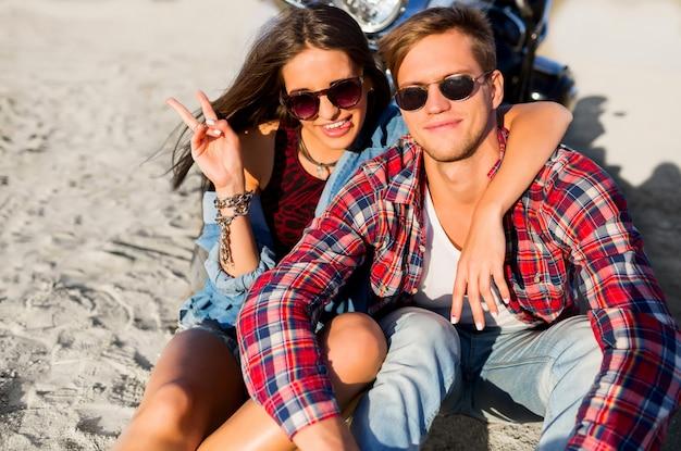日当たりの良いビーチでポーズをとって、バイクの近くで休んで、スタイリッシュな夏の服装、クールなサングラスを身に着けているカップルのライダーのファッションポートレートを閉じます。ロマンチックな気分。