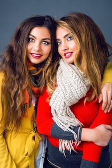 スタイリッシュなカジュアルな服と大きな暖かいスカーフを身に着けている流行の化粧品でエレガントなレースのファッションポートレートを閉じます。親友の姉妹の冬のファッションポートレート。