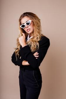 ベージュの壁でポーズスタイリッシュなカジュアルな黒のジャケットでゴージャスな金髪の女性のファッションの肖像画を閉じます。白いレトロなメガネ。ハイファッションスタイル。