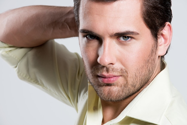 얼굴 근처 손으로 노란색 셔츠에 잘 생긴 남자의 근접 패션 초상화 포즈