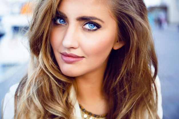 大きな青い目、完全な唇、完璧な肌、長いふわふわのカールしたヘアスタイルと魅惑的なセクシーな女性のファッションポートレートを閉じます。ナチュラルメイク。