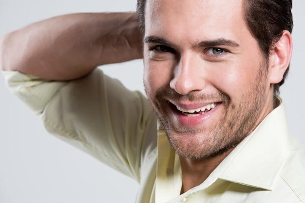 Крупным планом модный портрет улыбающегося человека в желтой рубашке с рукой возле позы лица