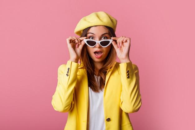 Крупным планом портрет моды стильная женщина в желтом костюме и берете.
