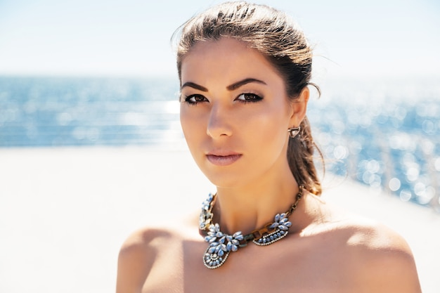 彼女の海の側をポーズスタイリッシュな大きなダイヤモンドネックレスの若い美しい女性のファッションの肖像画を閉じます。ライトクリーンカラー。