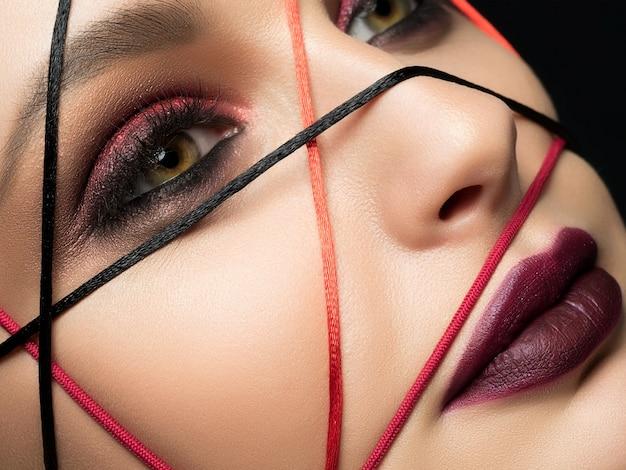 Крупным планом портрет моды молодой красивой женщины с современным модным макияжем