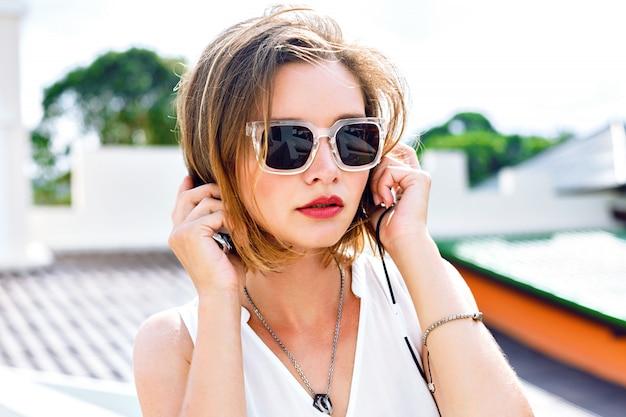 彼女のイヤホン、明るい化粧、新鮮な夏の色で彼女のお気に入りの音楽を聴く若いセクシーな女性のファッションポートレートを閉じます。屋上のポーズ、前向きな気分。