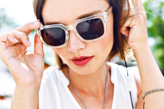 彼女のイヤホン、明るい化粧、新鮮な夏の色で彼女のお気に入りの音楽を聴く若いセクシーな女性のファッションポートレートを閉じます。