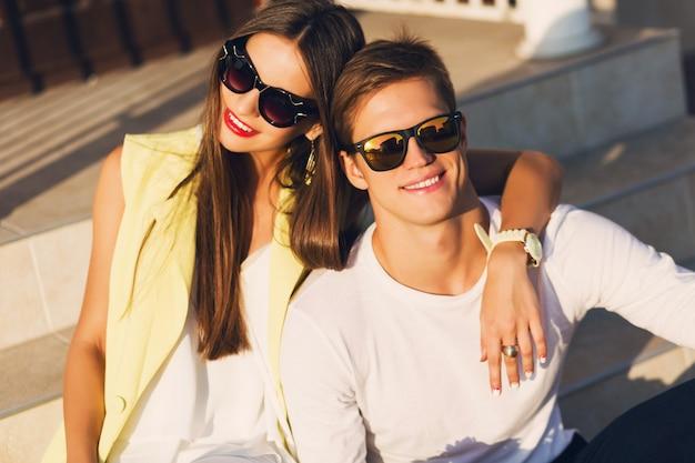 通りの屋外ポーズ、笑みを浮かべて、笑って、抱いて、一緒に時間を楽しんで恋にスタイリッシュな陽気なカップルのファッションの肖像画を閉じます。明るく暖かい日当たりの良い色。ロマンチックな気分。