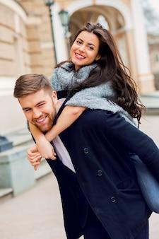 スタイリッシュなグラマー少女と恋の男のファッションポートレートを閉じます。晴れた秋の通りを歩いているカップル。暖かい秋の色。黒の流行の服を着ています。