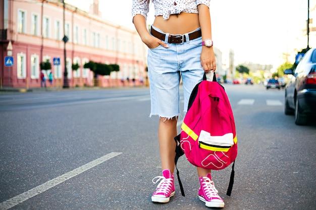 明るいバックパック、カジュアルな流行の服と一人で旅行、若いスタイリッシュな女性のファッションの肖像画を閉じます。通りを歩いている流行に敏感な女の子、ファッションの詳細