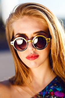 Close up fashion portrait of stunning blonde woman with big lips round sunglasses, bright sunny colors. wearing bright evening luxury dress.