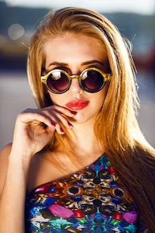 Close up fashion portrait of stunning blonde woman with big lips round sunglasses and long hairs, bright sunny colors. wearing bright evening luxury dress.