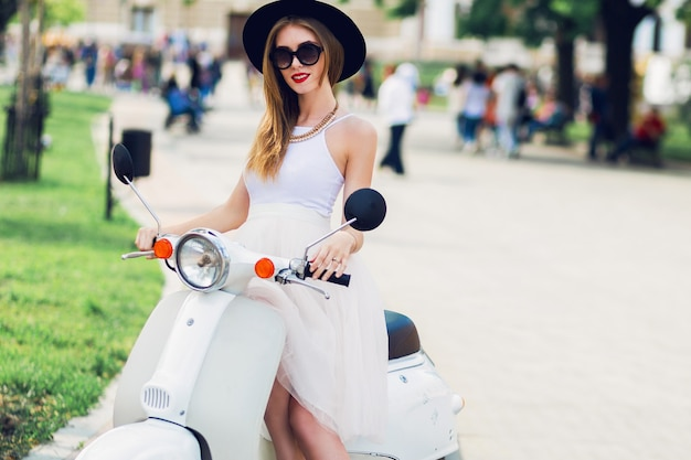 Close up fashion  portrait of young blonde woman in white tulle skirt and black heels sitting on vintage scooter.