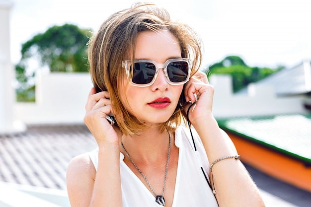 Close up fashion portrait of young sexy woman listening her favorite music in her earphones, bright makeup, fresh summer colors. posing at roof, positive mood.