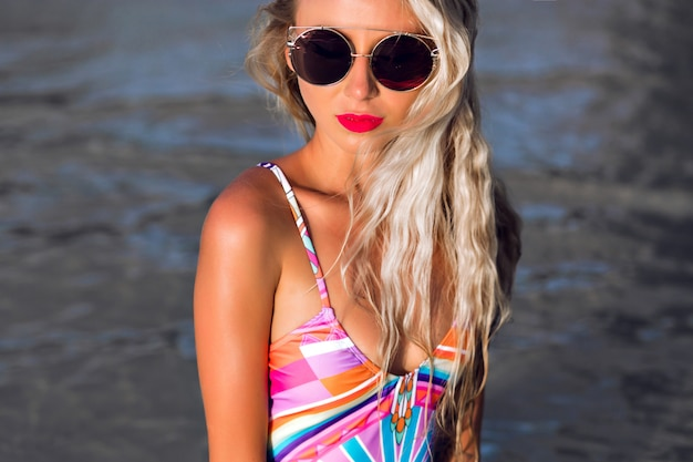 Close up fashion portrait of young stylish woman posing at summertime, reflection of beach and sea at her trendy fuchsia mirrored sunglasses, beautiful face and full red lips.