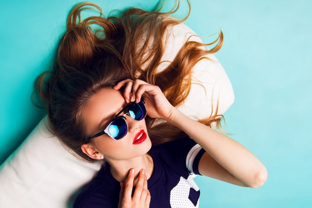 Close up fashion studio portrait of elegant beautiful woman with stylish sunglasses. red lips blue background.