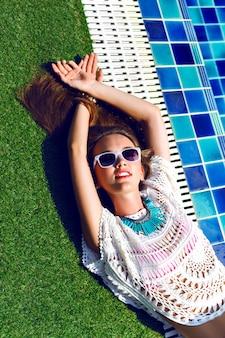 見事な美しい女性のファッション夏の肖像画を閉じて、プールの近くに敷設、リラックスして日光浴をします。トレンディなアクセサリーやジュエリー、贅沢なバカンススタイル、明るい色調。