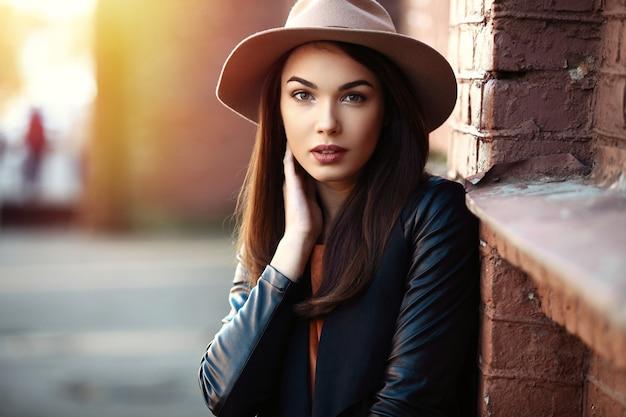 街でポーズをとる、かなりトレンディな若い女の子のクローズアップファッション女性の肖像画、秋のストリートファッション、60年代まで人気のレトロなフェドーラ帽を保持しています。笑って笑ってportrait.trendy