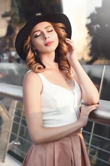 ヨーロッパの街でポーズをとる若いかなりトレンディな女の子のクローズアップファッション女性の肖像画