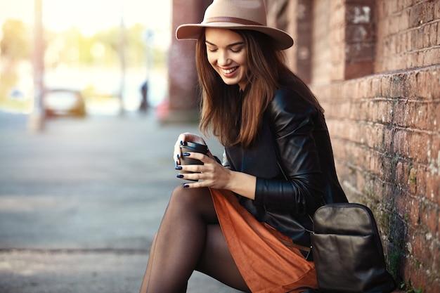 街でポーズをとる若いかなりトレンディな女の子のクローズアップファッション女性の肖像画