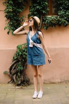 Close-up moda donna ritratto di giovane ragazza piuttosto alla moda in posa in città in europa, moda di strada estiva, con cappello fedora retrò popolare fino agli anni '60.