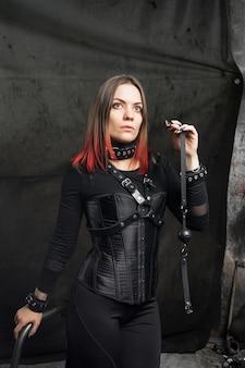 Крупным планом модный портрет модели в черном корсете и с кожаными ремнями.