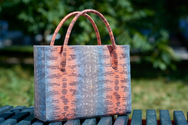 Close-up of fashionable woman s bag with snake skin imitation stands on the blue park bench . a bag was made in blue,pink and grey colors. also it has comfortable handles.