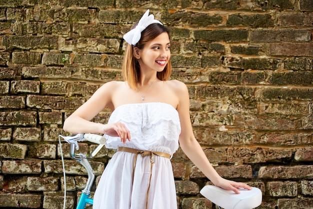 벽돌 벽에 빈티지 자전거와 근접 유행 여자