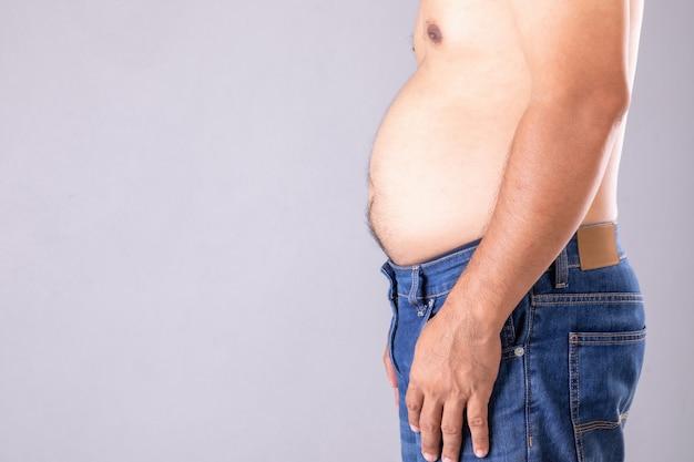 서있는 뚱뚱한 남자를 닫고 그의 배를 보여줍니다. 뚱뚱한 사람과 건강한 개념