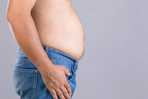 Close up fat man standing and show his tummy with. fat people and healthy concept