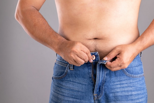 버튼 업 바지를 시도하는 뚱뚱한 남자를 닫습니다