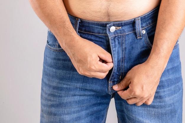 Крупным планом толстый мужчина пытается застегнуть свои синие джинсовые брюки