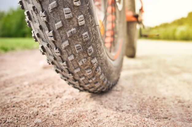 Close-up of fat mountain bike tire on dirty road. fat bike wheel. summer outdoor activity concept.