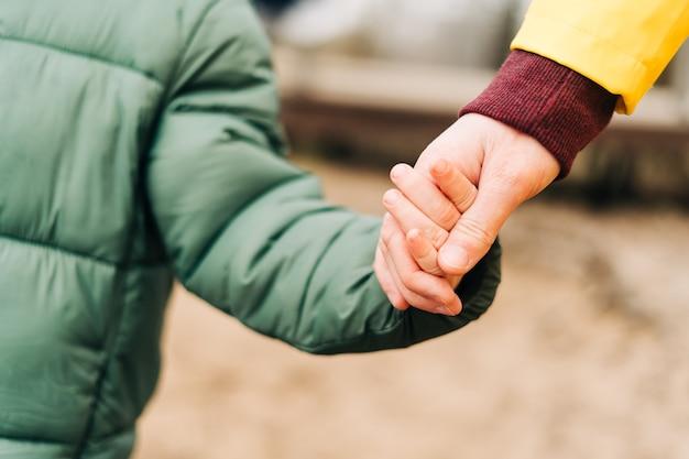 Крупным планом отец и сын стоят на берегу озера и держатся за руки счастливая семья с ребенком-малышом