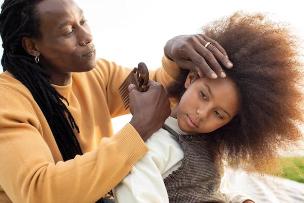 Primo piano padre che spazzola ragazza